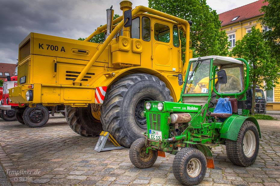 Große Landmaschine und kleiner Traktor auf dem Markt in Templin nebeneinander